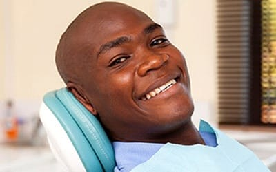 A man smiling in a dental chair.